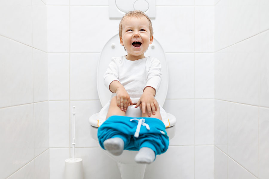 Adorable young child sitting on the toilet at a Preschool & Daycare Serving North Hollywood, Santa Monica & Van Nuys, CA