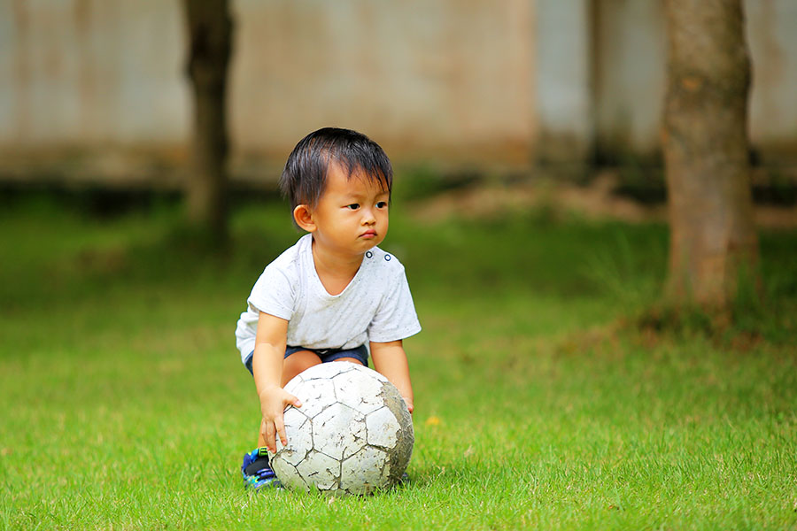 Asian boy playing football at a Preschool & Daycare Serving North Hollywood, Santa Monica & Van Nuys, CA