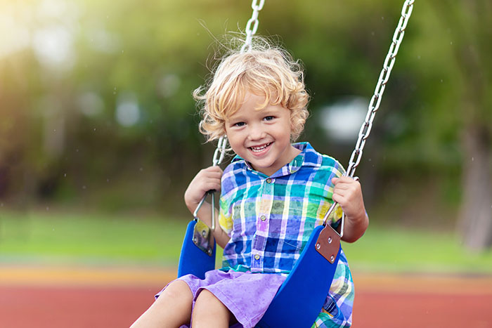 smiling boy on swings at playground at a Preschool & Daycare Serving North Hollywood, Santa Monica & Van Nuys, CA